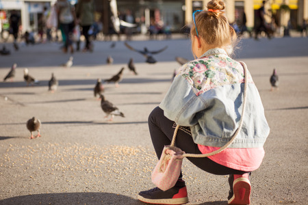 modern young girl feeding pigeons on the city square Banque d'images