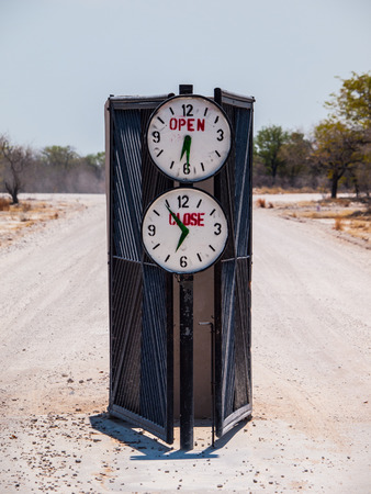 closing time: Campsite gate with marked opening and closing time (Halali, Etosha National Park, Namibia) Stock Photo
