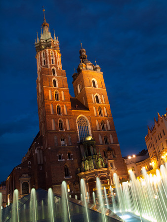 St. Marys Church with two different towers by night (Krakow, Poland). Viewed from fountain.