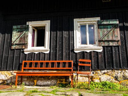 doorstep: Brown bench at doorstep of wooden cottage