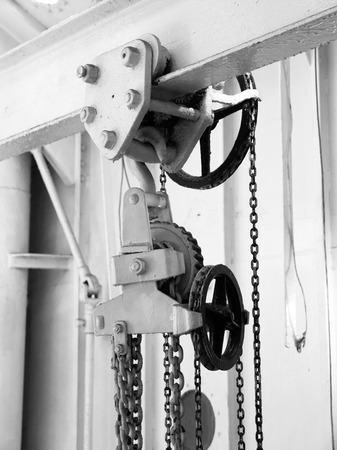 grey scale: Metal pulley with chains, detailed close-up view in black and white Stock Photo