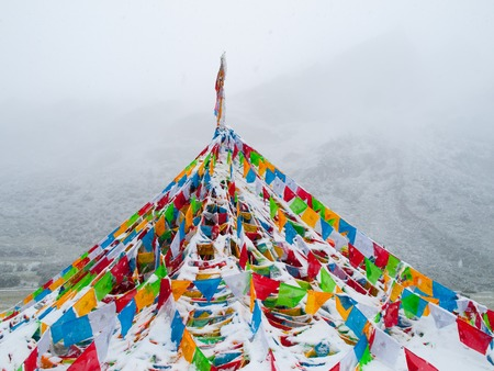 Buddhist tibetan prayer flags in snowy and foggy weather photo