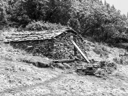 grey scale: Mountain stone shelter for tourist, bivouac, Yading reserve, Daocheng, Sichuan, China, black and white image Stock Photo