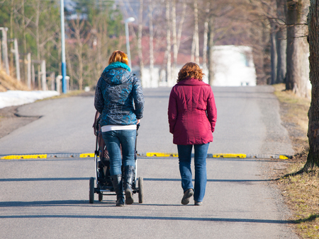 unplanned: Two women walking towards speed bump with pram in sunny day Stock Photo