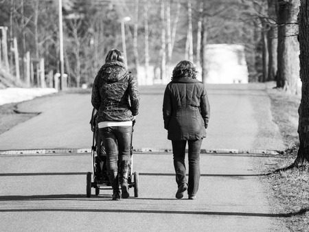 maternity leave: Two women walking towards speed bump with pram in sunny day, black and white image
