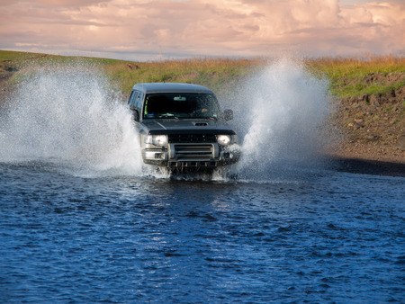 Offroad car fording the river and water splash, front view