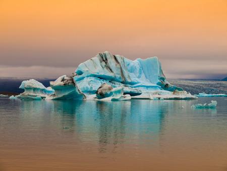 Blue icebergs in Jokulsarlon Glacier Lagoon inevening red sunlight, Iceland