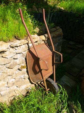 wheelbarrow: Old rusty garden wheelbarrow leaned on the wall after work