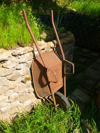 carretilla: Oxidada vieja carretilla jardín se apoyó en la pared después del trabajo