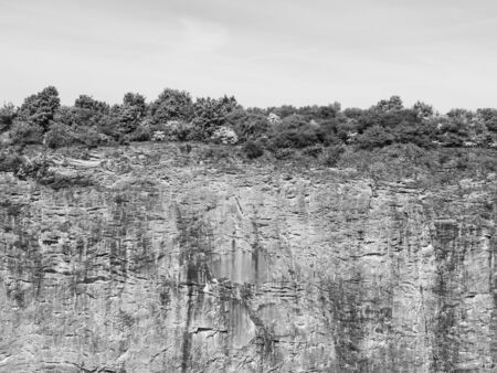 end of world: End of the World, vertical stone wall of old lime quarry with bush on the edge, black and white image