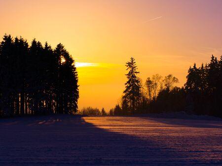 resfriado: La puesta del sol del invierno en paisaje con �rboles, colores c�lidos Foto de archivo