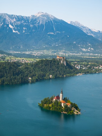 Bled lake with island church and Bled castle, mountains in background, Slovenia