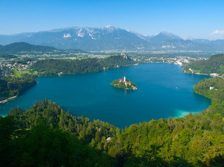 Aerial view of Bled Lake with island church and Bled Castle, mountains in background, Slovenia