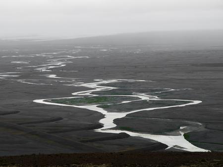 meandering: Black glacier flood plain called sandur and meandering river flowing into the sea, Skaftafell National Park, Iceland