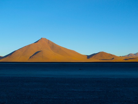 lipez: Brown peaks of Cordillera de Lipez illuminated by rising sun. Rest of the ground is in the shadow. Laguna Colorada, Bolivia