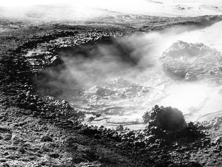 escaping: Steam escaping from mudpot and illuminated by sun rays, Sol de Manana, Altiplano, Bolivia, black and white image