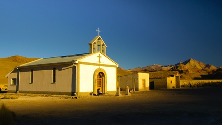 lipez: Small white church and woman sitting in front of it in Cordillera de Lipez in southern bolivian Altiplano. The church looks like from western movie.