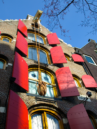 Amsterdam house with red window shutters and rope hanging on the hook, Netherlands