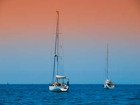 anchoring: Two yachts anchoring on a blue sea in the evening time
