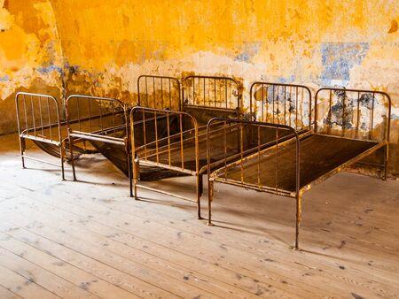 terezin: Quattro vecchi letti arrugginiti in stanza abbandonata Archivio Fotografico