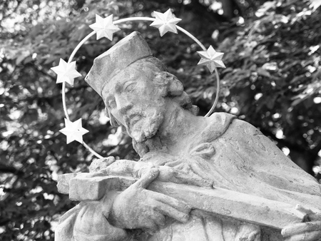 black hands: Detailed view of statue of saint with halo and green trees on background. Black and white image.