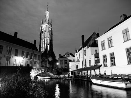 bridge over water: Church of Our Lady and bridge over water canal at night, Bruges, Belgium. Black and white image.