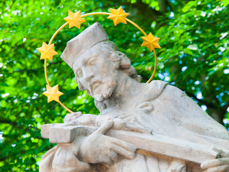 gloriole: Detailed view of statue of saint with golden halo and green trees on background