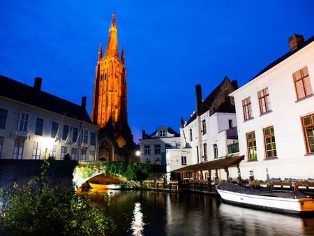 bridge over water: Church of Our Lady and bridge over water canal at night, Bruges, Belgium Stock Photo
