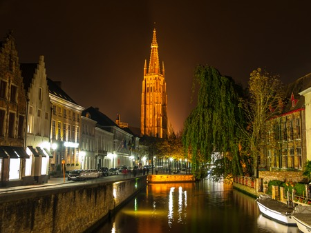church of our lady: Church of Our Lady and bridge over water canal at night, Bruges, Belgium Stock Photo
