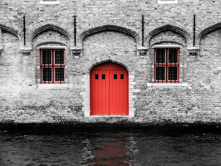 red door: Red door and two windows at water canal. Typical architecture of Bruges, Belgium.