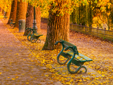 footpath: Beautiful ornamental green benches in autumn park Stock Photo