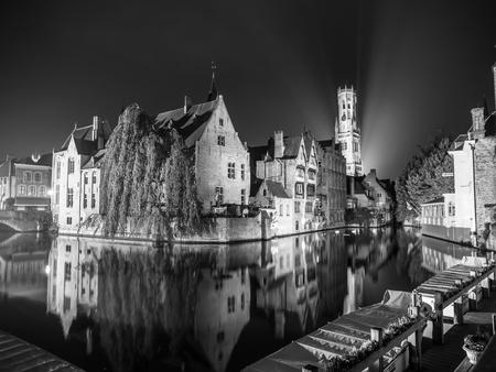belfort: The dock of Rosary - Rozenhoedkaai - and Belfort Tower at night, Bruges, Belgium. Black and white image.