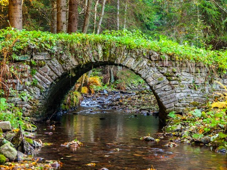 Picturesque old stone bridge over calm brook in an autumn forest
