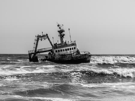 barca da pesca: Naufragio sulla Skeleton Coast dell'Oceano Atlantico in Namibia. Immagine in bianco e nero.