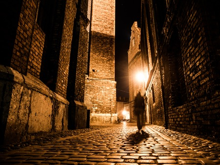 street: Illuminated cobbled street with light reflections on cobblestones in old historical city by night. Dark blurred silhouette of person evokes Jack the Ripper.