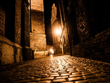 Illuminated cobbled street with light reflections on cobblestones in old historical city by night Stockfoto
