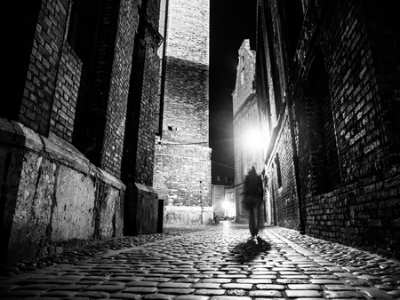 ripper: Illuminated cobbled street with light reflections on cobblestones in old historical city by night. Dark blurred silhouette of person evokes Jack the Ripper. Black and white image.