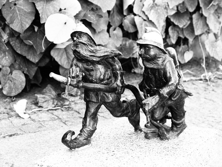 dwarfs: WROCLAW, POLAND - CIRCA 2014: Two dwarf firemen figurines in Wroclaw city centre, circa 2014. Dwarfs are small figurines hidden on different places in Wroclaw. Black and white image. Editorial