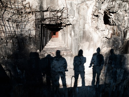 embrasure: Loophole in old military bunker and shadows of men on devasted wall