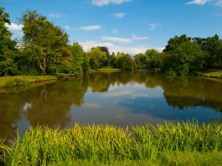 unesco in czech republic: Park pond with blue trees and summer blue sky, Lednice-Valtice Cultural Landscape, Czech Republic Stock Photo