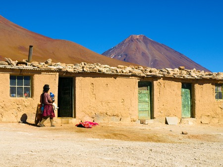 lipez: Basic house made of adobes and bolivian woman in typical dress. Licancabur volcano on background, Altiplano, Bolivia.