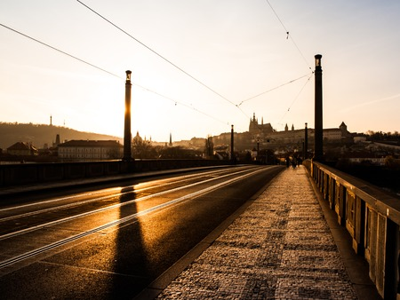 manes: Evening is hidden behind column on Manes Bridge with silhouette of Hradcany, Prague, Czech Republic Stock Photo
