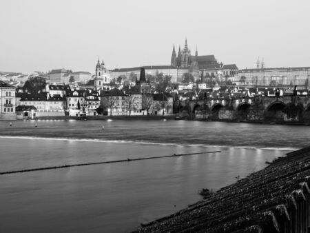 morning blue hour: View of Prague Castle, Charles Bridge and Vltava River in early morning blue hour, Czech Republic. Black and white image.