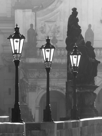 mood moody: Street lamps on Charles bridge illuminated by morning sun and dark silhouettes of statues, Prague, Czech Republic. Black and white image.