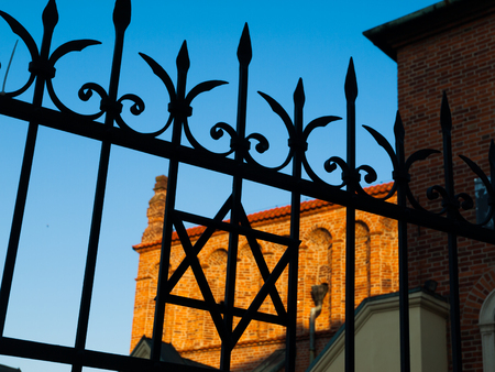 judaical: Detailed view of iron gate with David star and part of Old Synagogue on background, Krakow, Poland Stock Photo