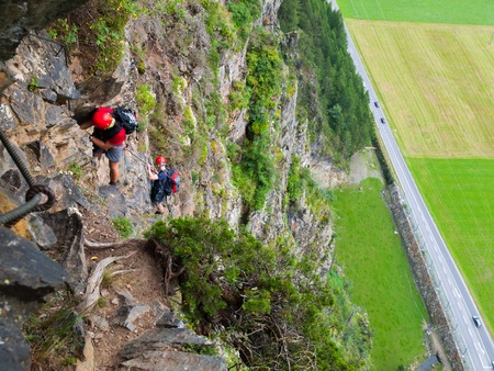 steel cable: Via ferrata climbers holds steel cable high above road, Reinhard Schiestl Klettersteig, Austria