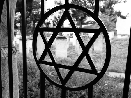 judaical: Iron gate with David star at jewish cemetery, Krakow, Poland. Black and white image.