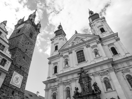 gildhall: Black Tower and The Church of Virgin Marys Immaculate Conception and St. Ignatus in Klatovy, Czech Republic . Black and white image. Stock Photo