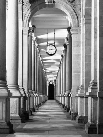 colonade: Long colonnafe corridor with columns and clock hanging from ceiling