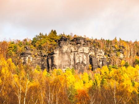 czech switzerland: Sandstone rock formation in the middle of colorful autumn forest. Dramatic evening view. Tisa Rocks, aka Tiske Walls, Czech-Saxon Switzerland, Czech Republic